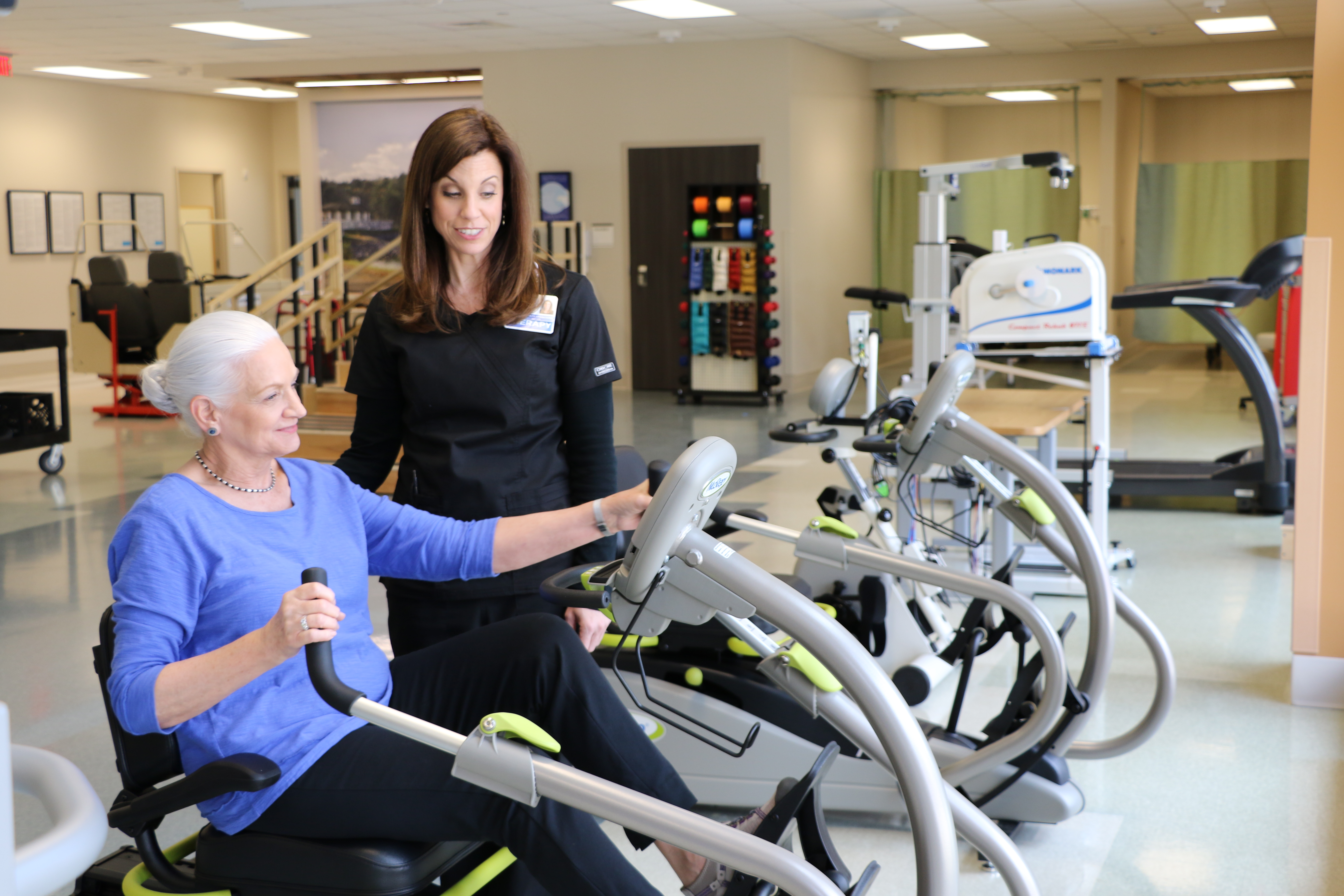 Female patient works on endurance, mobility and strength on the exercise bike in therapy gym with guidance from her female physical therapist