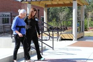 Female patient with walking cane and her therapist practice mobility skills in the hospital's outdoor courtyard