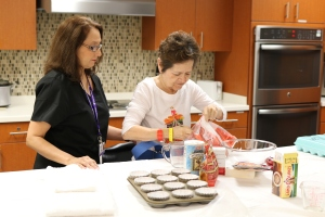 Female therapist works with female patient on making muffins in the activities of daily living kitchen at inpatient rehabilitation hospital