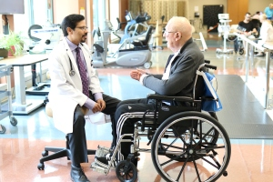 Male physician is seated and communicating with a male patient seated in a wheelchair. The conversation is taking place in the therapy gym where other therapies are taking place.