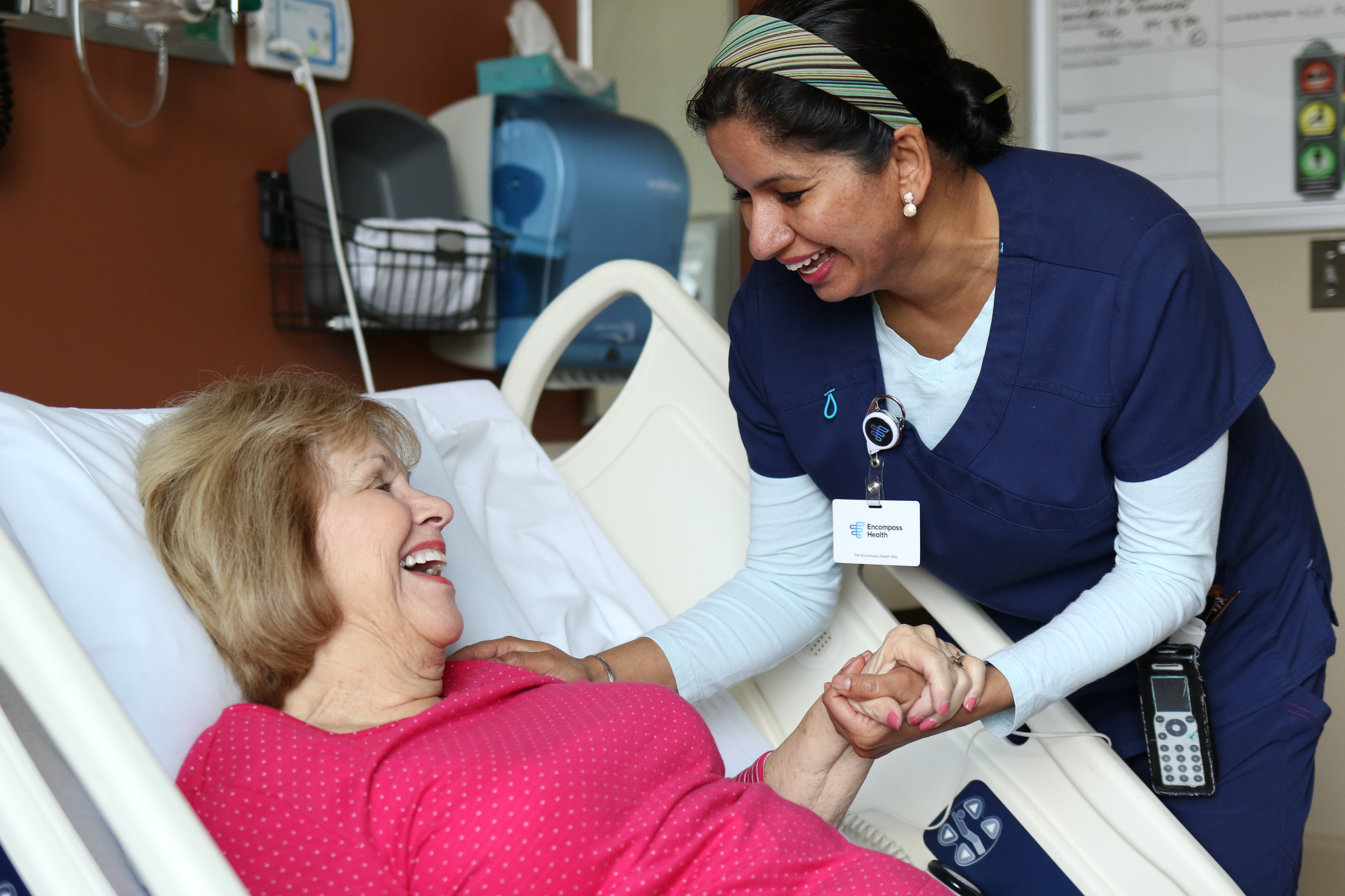 Middle-aged Caucasian female patient lays in hospital bed while female nurse wearing scrubs hold her hand and talks to her