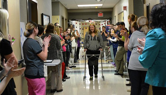 Patient Skyler Grey walks down the hospital halls as employees cheer her on.