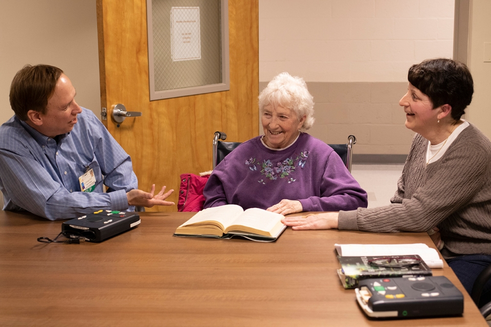 Dr. Steve Belanger discusses a book with two female patients.