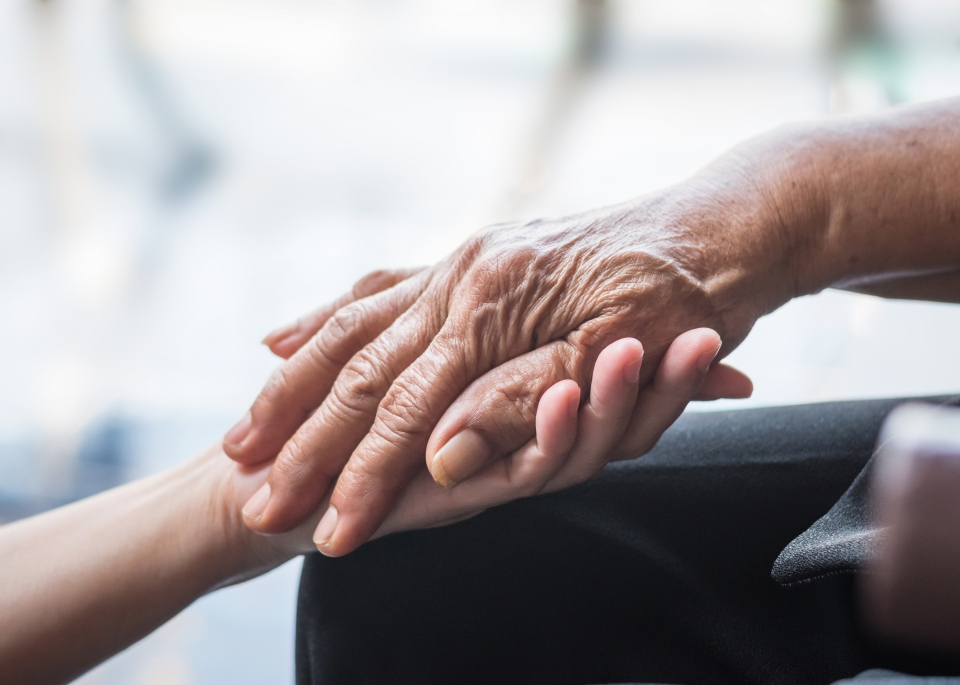 Hospice volunteer holding hands with patient