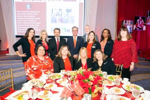 Many people wearing red business attire gather around a table
