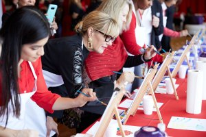 Several women paint on easels
