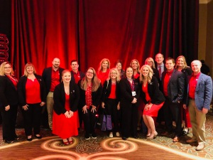 Many people wearing red business attire pose in front of a red curtain