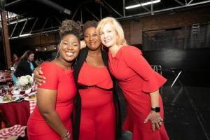 Three women wearing red embrace