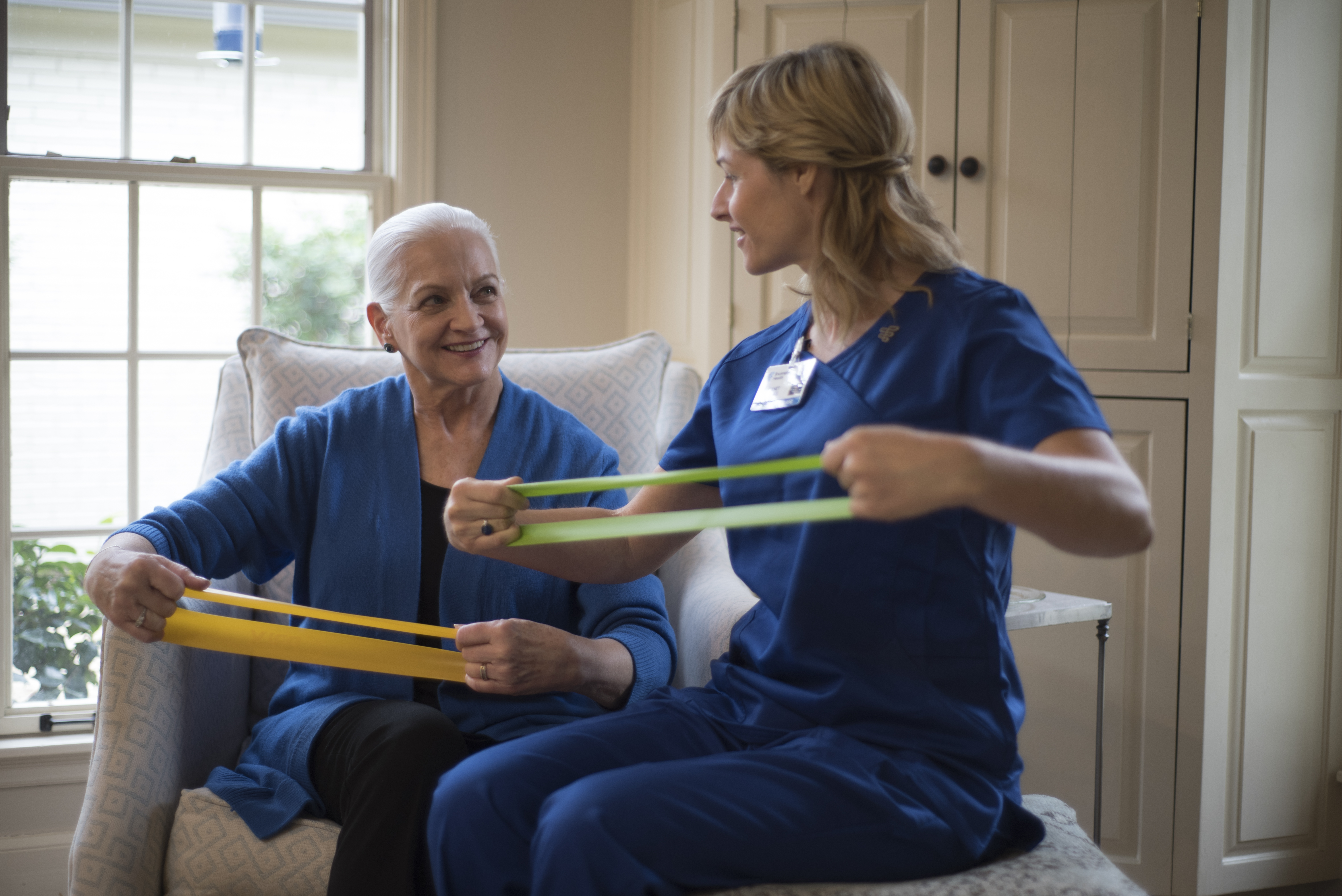 A therapist and a female patient practice stretching bands