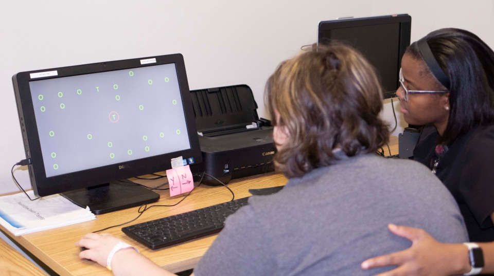 Alicia Wright, occupational therapist assistant, works with a patient on the NeruoEyeCoach.