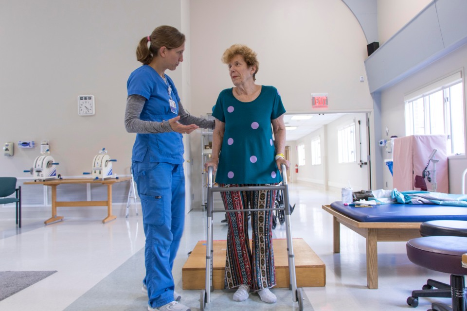 Heather Barackman, PT, helps a patient navigate raised surfaces with a walker.