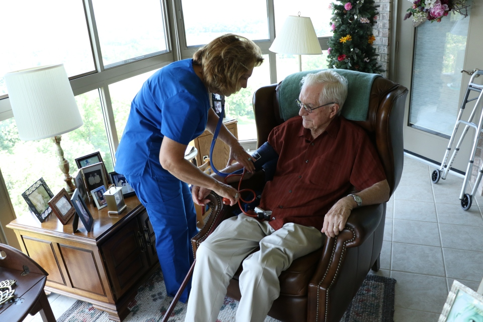 An Encompass Health Home Health employee checks a patient's vitals in the comfort of their home.