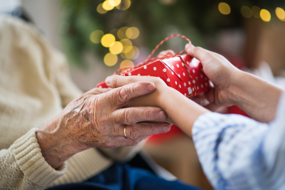 Close-up of hands of senior and young woman holding a present at Christmas time.