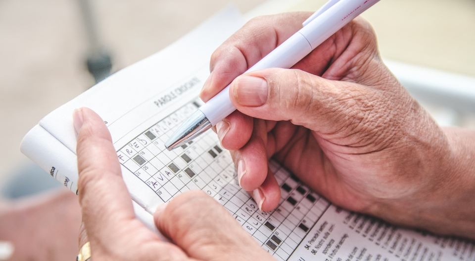 View of a person completing a crossword puzzle.
