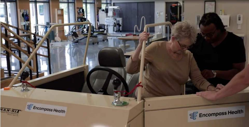A patient practices getting in and out of a car in an Encompass Health therapy gym.