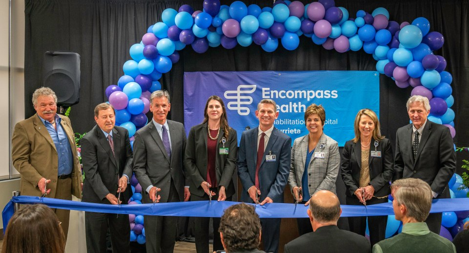 Eight professionals in business attire cutting blue ribbon in front of purple and blue balloon arch
