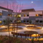 Outdoor courtyard at dawn with cotton candy skies and a lit pathway