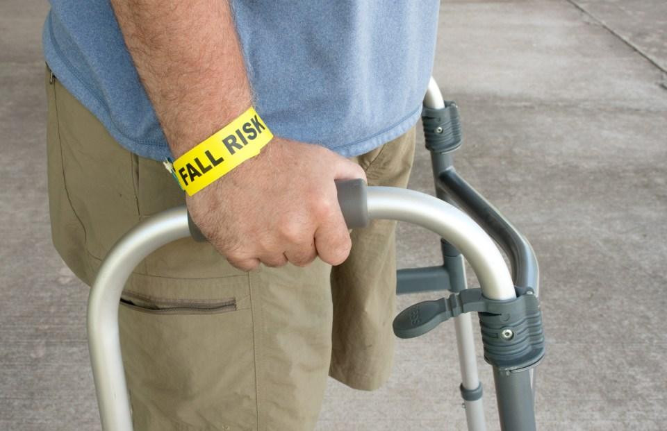 A man wearing a fall risk bracelet around his wrist using a walker