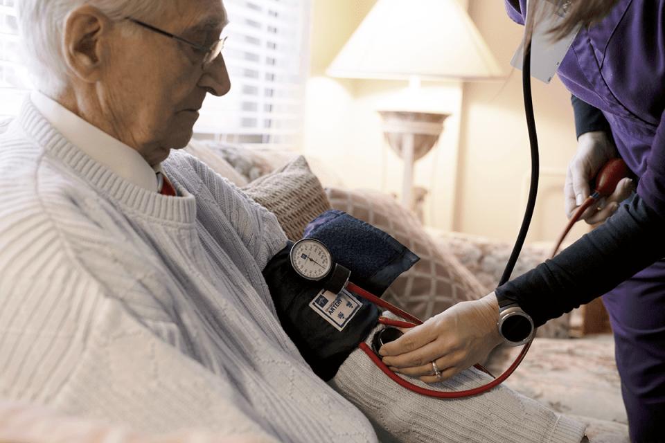 A nurse checks a patient's blood pressure
