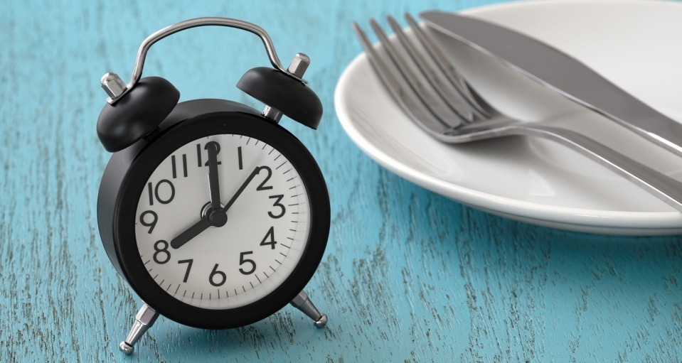 Clock with fork and knife on plate