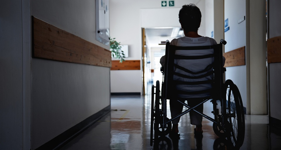A woman in a wheelchair sits alone in a hallway