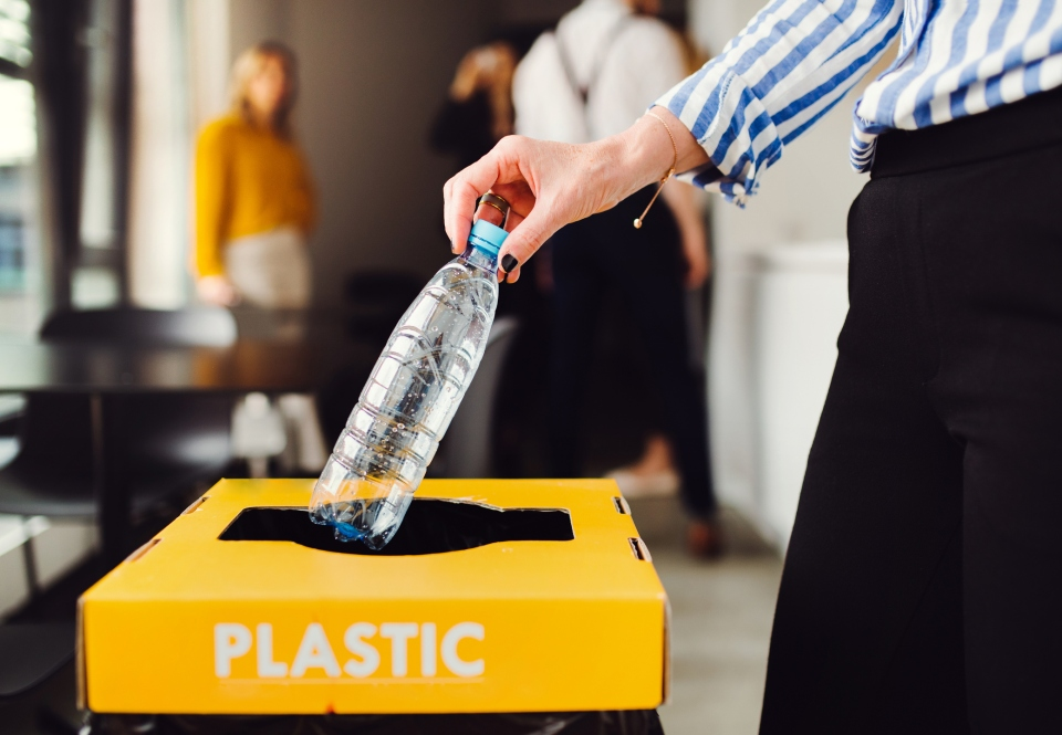 Person throwing plastic bottle into recycling bin