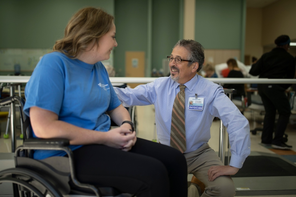 Male physician visits female patient in therapy gym