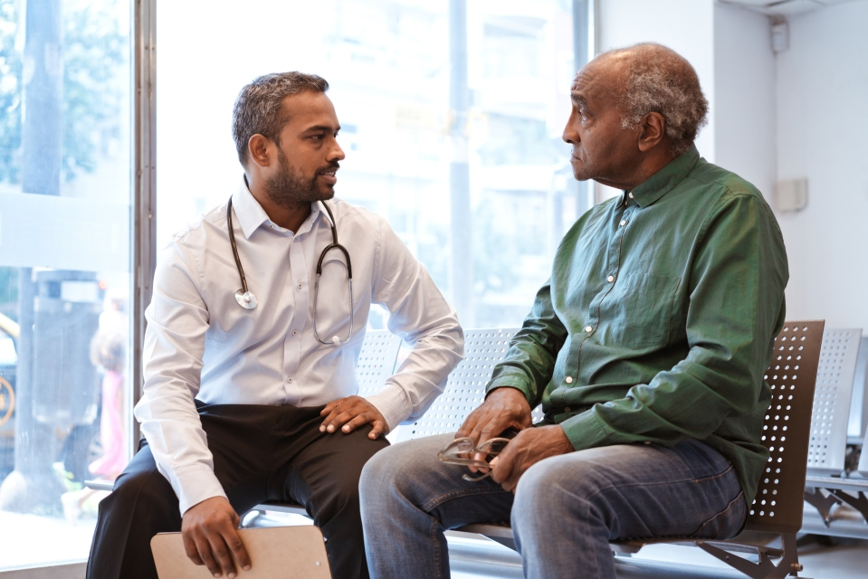 Doctor talking to senior patient sitting in waiting room.