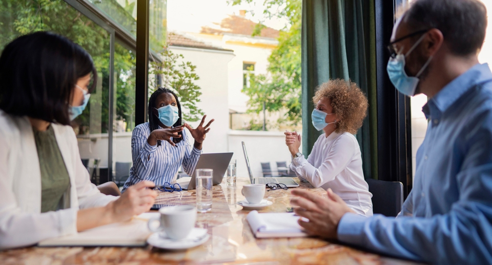 Diverse group of business people sitting together and having a meeting at the coffee shop. Brainstorming while wearing protective masks during a pandemic.