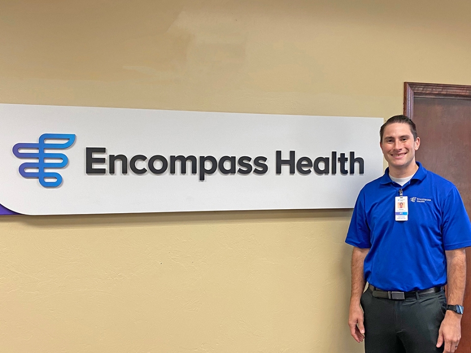 Physical therapist Trevor Baker stands in front of an Encompass Health sign