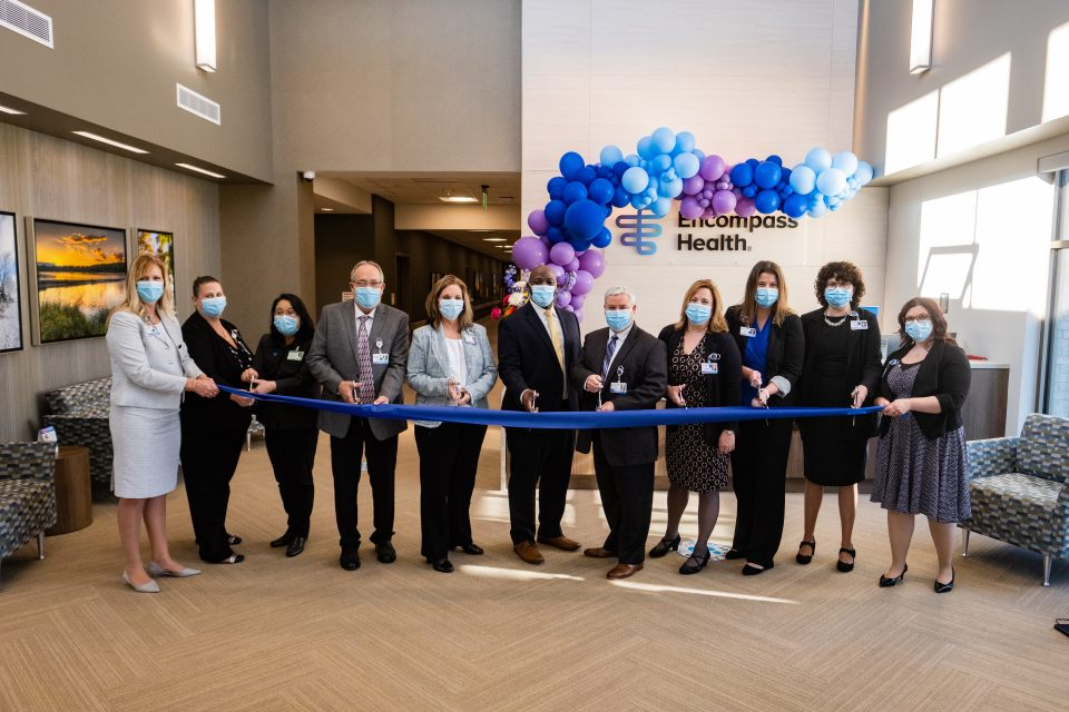 Leadership team inside hospital lobby cutting blue ribbon