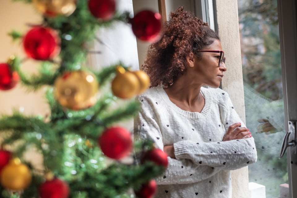 Woman stands behind Christmas tree staring out window.