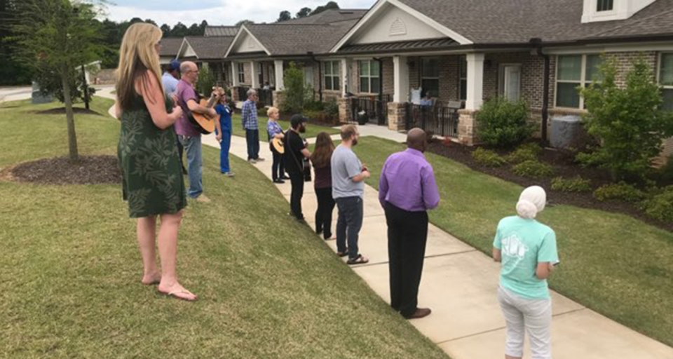 Encompass Health staff and volunteers in Aiken, SC sing outside a local independent living facility.