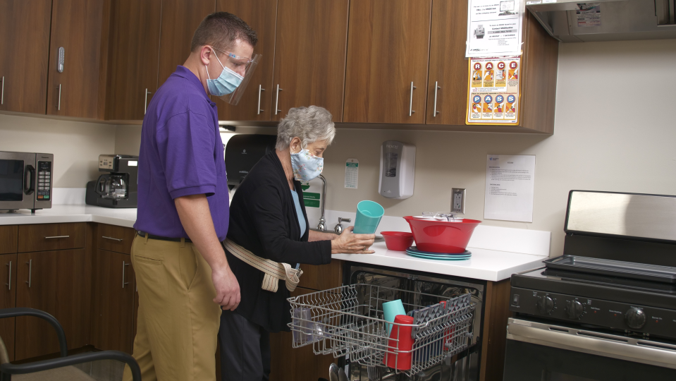 Female patient loads dishwasher while male therapist in purple polo and facemask looks on and supports her from falling