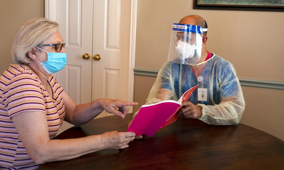 A clinician in personal protective equipment evaluates a patient in his home