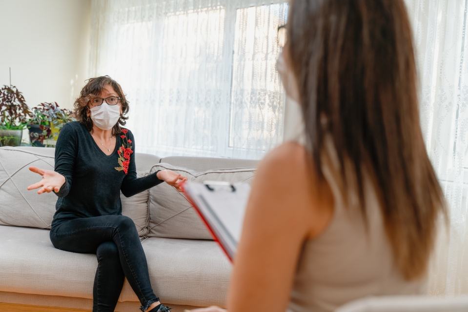 Woman wearing face mask sitting on the armchair and talking to the professional psychologist while wearing face mask conducting a consultation and making notes during coronavirus or COVID 19 outbreak