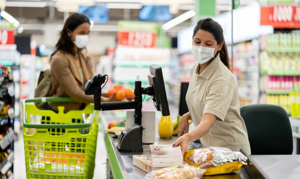 Latin American cashier scanning products at a grocery store wearing a facemask - quarantine lifestyle concepts
