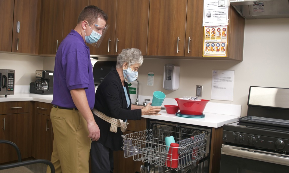 An Encompass Health therapist helps a patient load a dishwasher