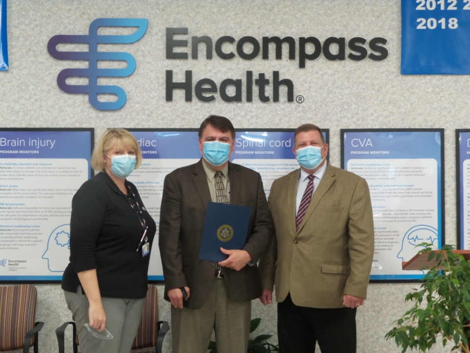 Three people in suits stand in front of Encompass Health logo and the man in the center holds award