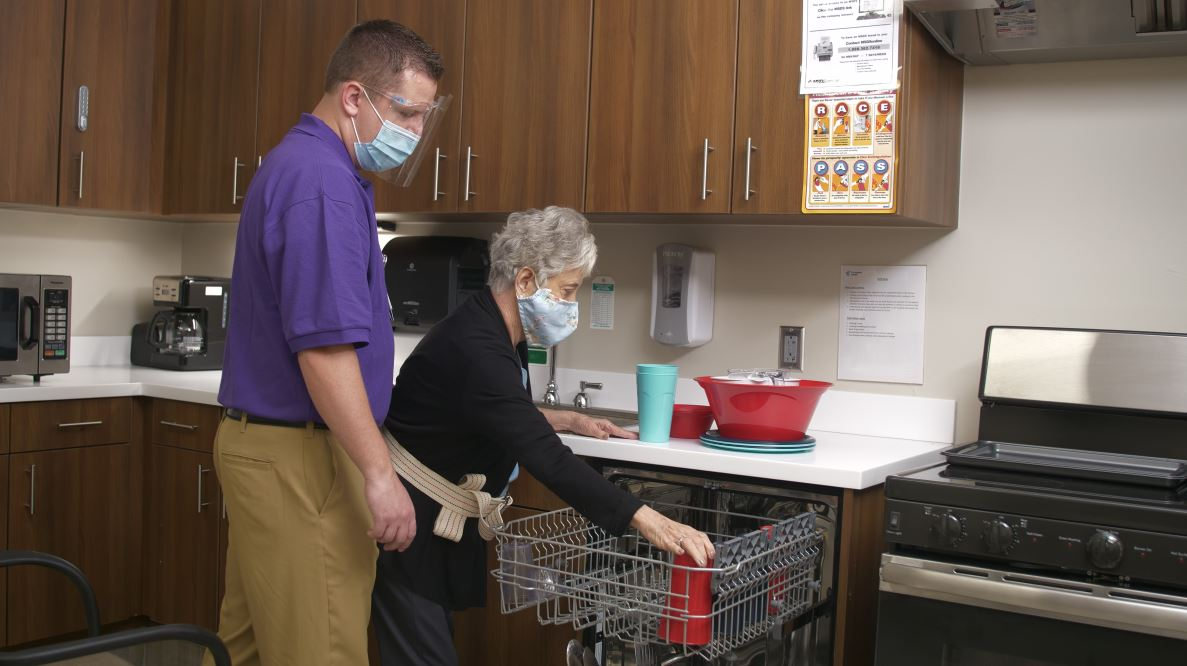 Male therapist working with female patient in a mock kitchen setting. Patient is practicing loading dishes into the dishwasher