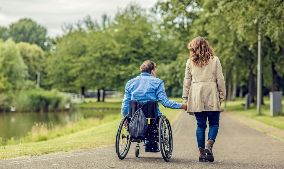 Wheelchair using young man and his girlfriend walking together through a city park on a sunny afternoon