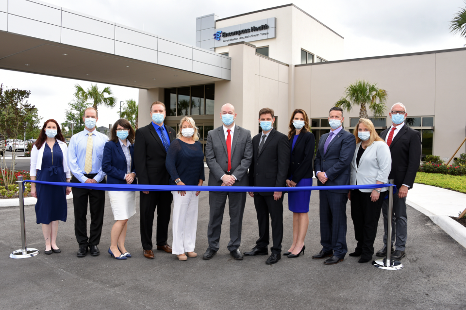 Eleven people in business attire standing in front of hospital