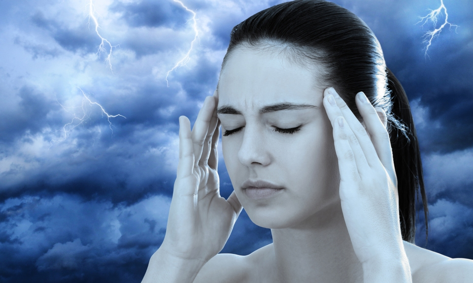 Close up conceptual portrait of young unhappy woman against dark clouds with lightning. Girl with headache and eyes closed.