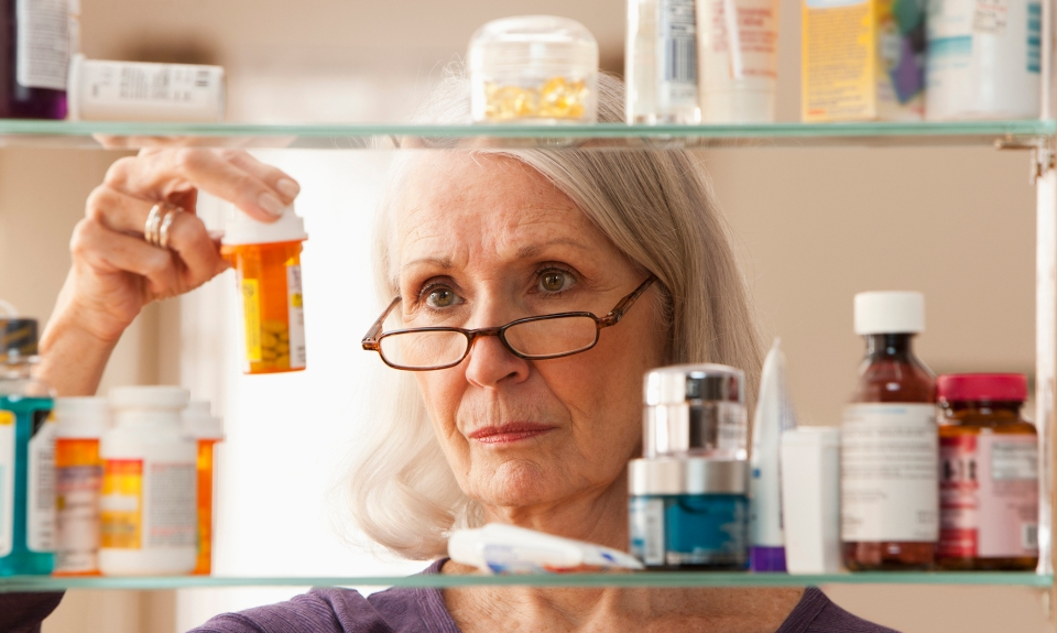 An older woman takes time to clean out her medicine cabinet