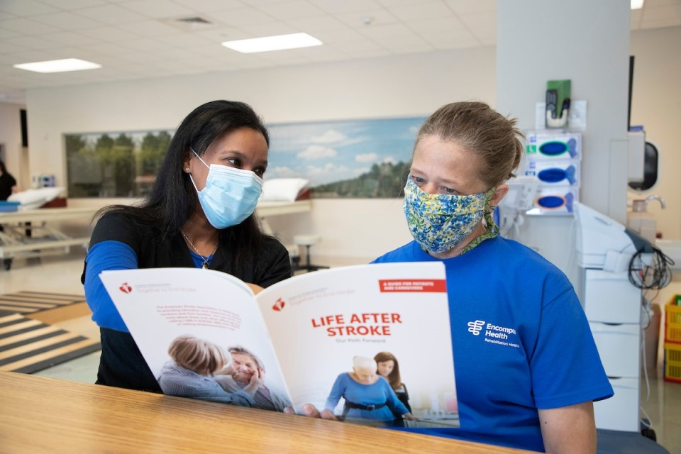 Therapist reading over information with female patient in blue T-shirt
