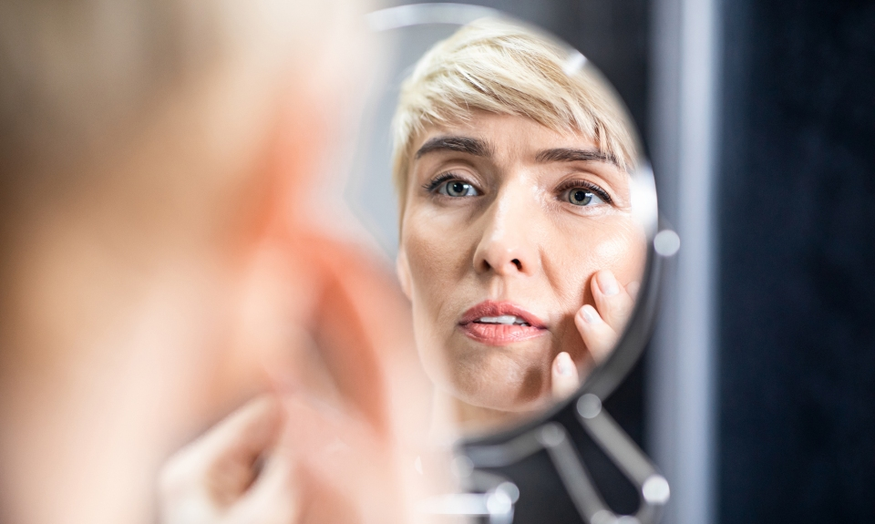 A woman checking her aging in the mirror