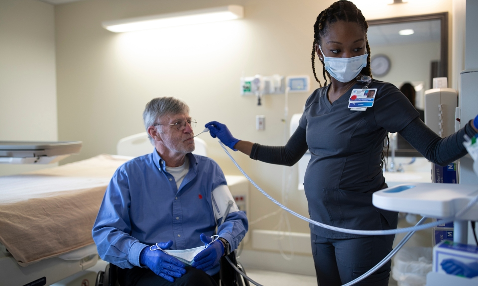 A rehabilitation nurse takes the temperature of a patient