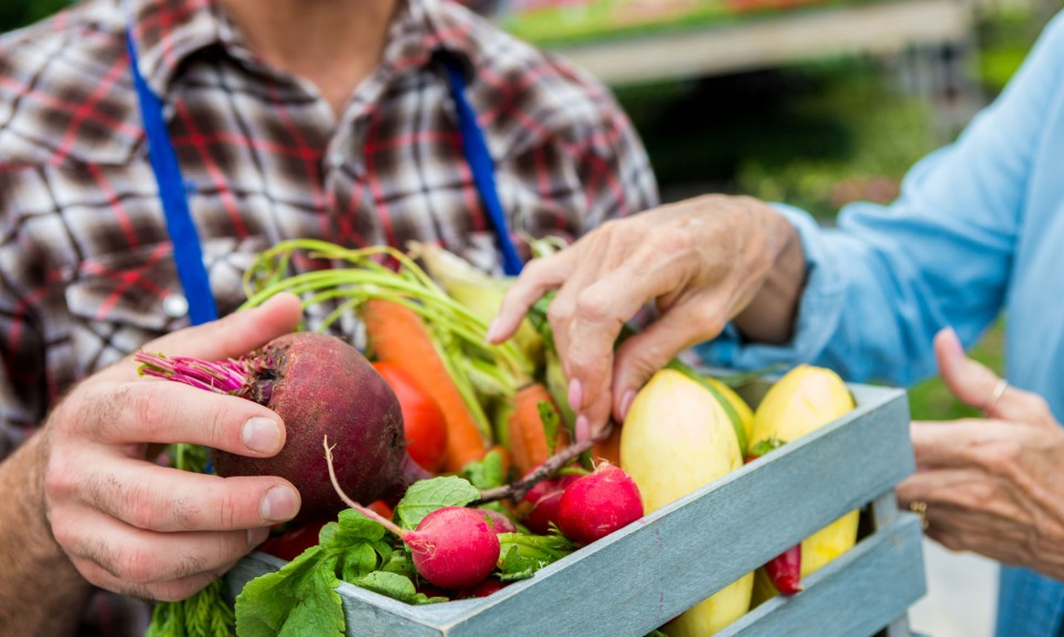 Shopper purchases box of produce at farmers market.