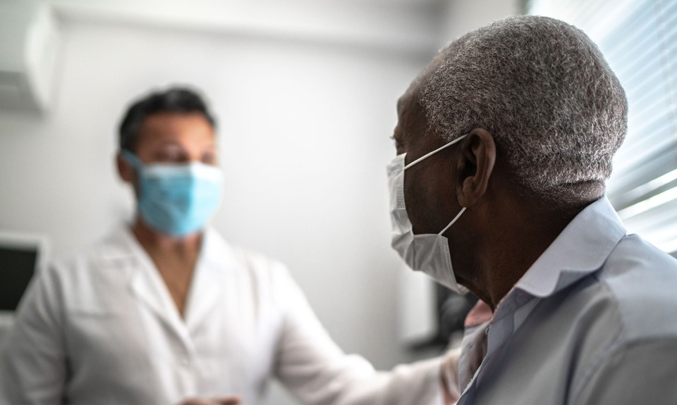 Doctor comforts patient while in office.