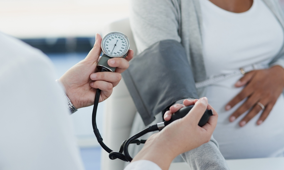 Doctor takes blood pressure of pregnant patient.